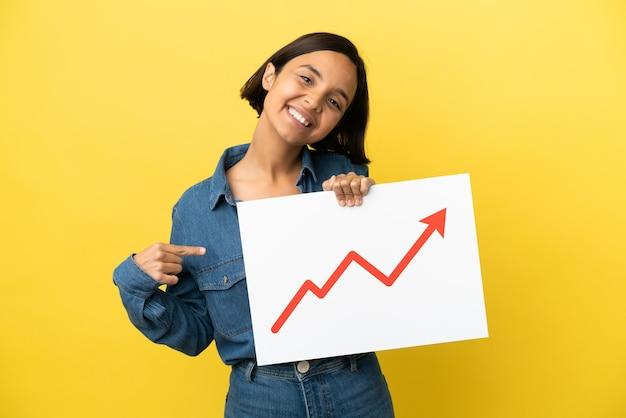 Giovane donna di razza mista isolata su sfondo giallo con un cartello con un simbolo di freccia di statistiche in crescita e indicandolo