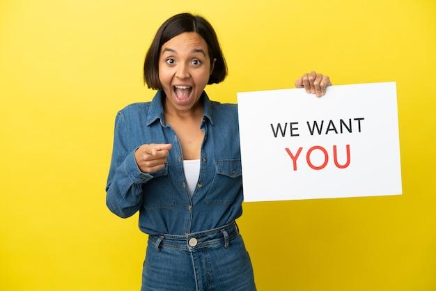 Giovane donna di razza mista isolata su sfondo giallo che tiene scheda we want you e punta verso la parte anteriore