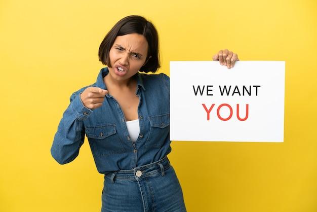 Giovane donna di razza mista isolata su sfondo giallo tenendo we want you board e indicando la parte anteriore