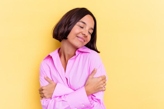 Giovane donna di razza mista isolata su sfondo giallo abbracci, sorridendo spensierata e felice.