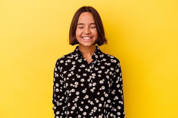 La giovane donna di razza mista isolata su sfondo giallo ride e chiude gli occhi, si sente rilassata e felice.
