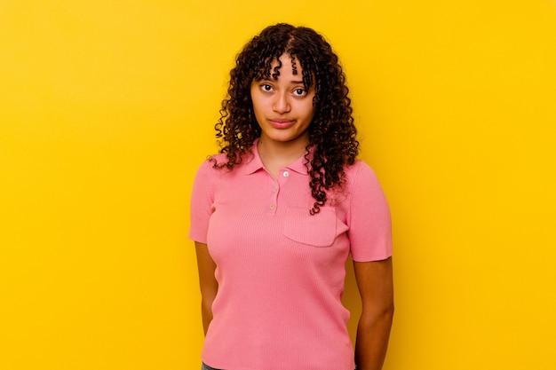 Giovane donna di razza mista isolata su sfondo giallo, faccia triste e seria, sentendosi infelice e scontenta.
