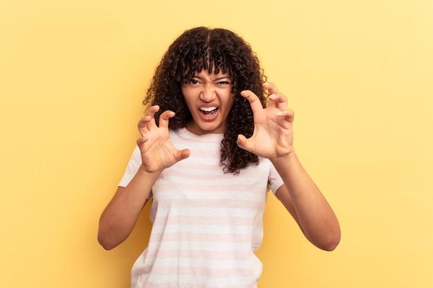 Giovane donna di razza mista isolata su sfondo giallo che mostra artigli che imitano un gatto, gesto aggressivo.