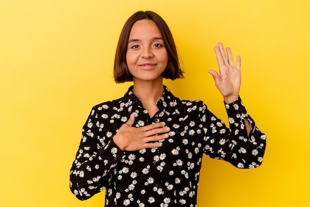 Giovane donna di razza mista isolata su sfondo giallo prestando giuramento, mettendo la mano sul petto.
