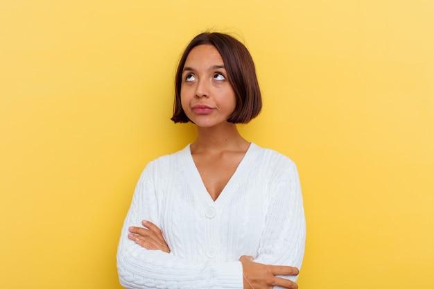 Giovane donna di razza mista isolata su sfondo giallo stanco di un compito ripetitivo.