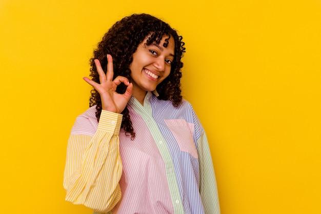 La giovane donna di razza mista isolata su priorità bassa gialla strizza l'occhio e tiene un gesto giusto con la mano.