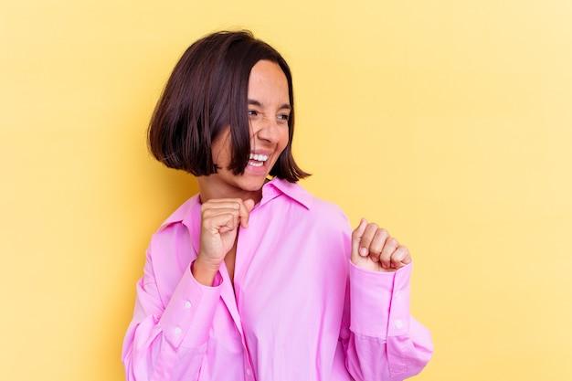 Giovane donna di razza mista isolata sul muro giallo ballando e divertendosi
