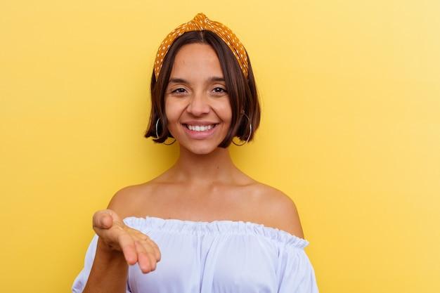 Giovane donna di razza mista isolata sul muro giallo che allunga la mano davanti nel gesto di saluto.