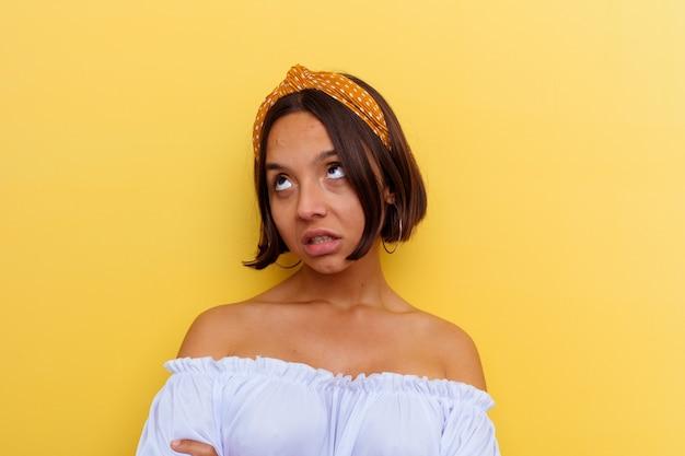 Giovane donna di razza mista isolata sul muro giallo stanca di un compito ripetitivo.