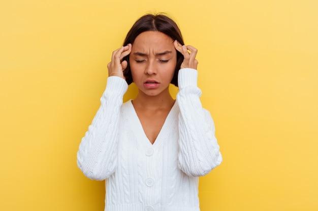 Giovane donna di razza mista isolata sul muro giallo, toccando le tempie e avendo mal di testa.