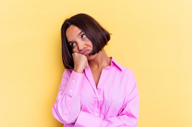 Giovane donna di razza mista isolata sul muro giallo che si sente triste e pensierosa, guardando lo spazio della copia.