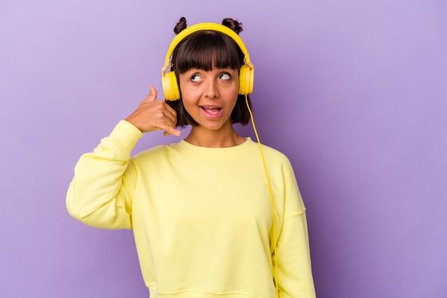 Giovane donna di razza mista che ascolta musica isolata su sfondo viola che mostra un gesto di chiamata di telefonia mobile con le dita.