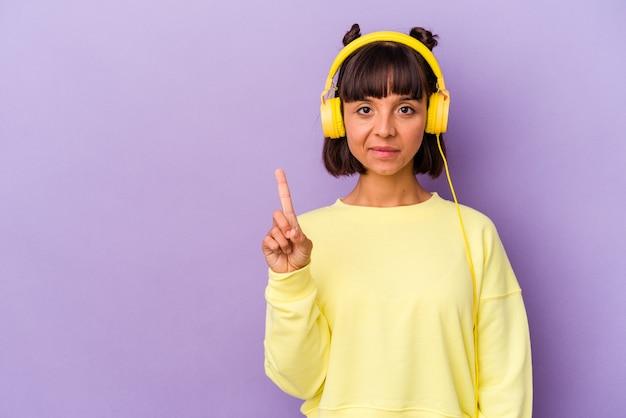 Giovane donna di razza mista che ascolta musica isolata su sfondo viola che mostra il numero uno con il dito.