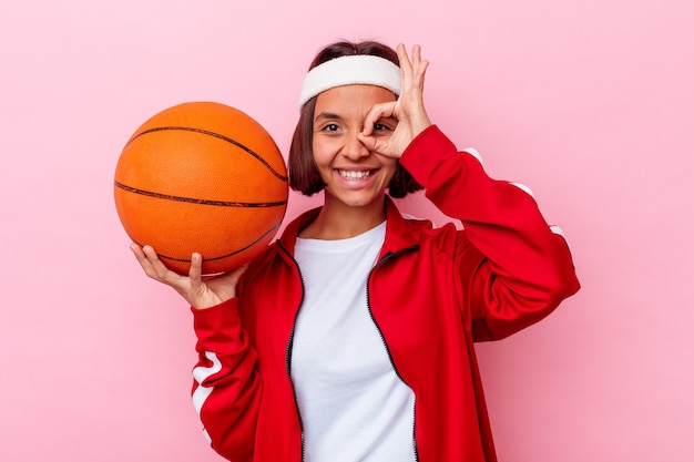 Giovane donna di razza mista che gioca a basket isolato su sfondo rosa eccitato mantenendo il gesto giusto sull'occhio.
