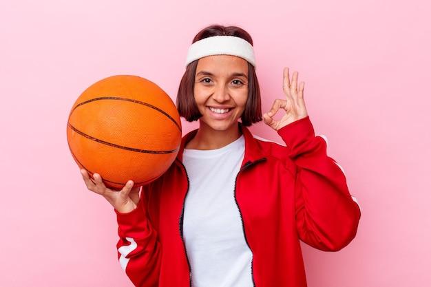 Giovane donna di razza mista che gioca a basket isolato sul muro rosa allegro e fiducioso che mostra gesto giusto.