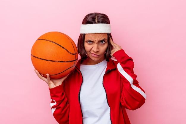 Giovane donna di razza mista che gioca a basket isolato sul muro rosa che punta il tempio con il dito, pensando, concentrato su un compito.