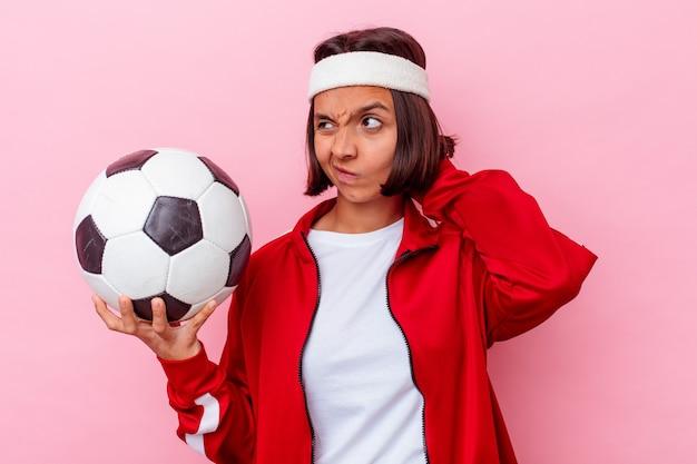 Giovane donna di razza mista che gioca a calcio isolato sul muro rosa che tocca la parte posteriore della testa, pensando e facendo una scelta.