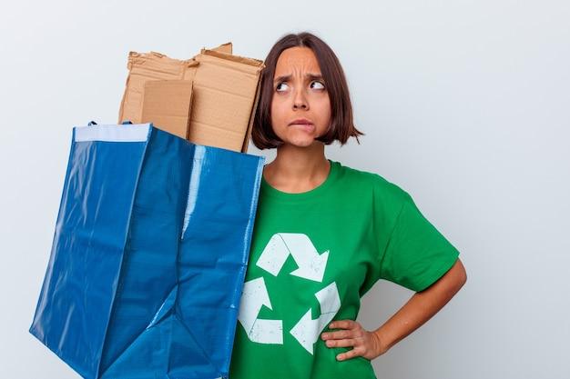 Giovane donna di razza mista che ricicla il cartone isolato sul muro bianco confuso, si sente dubbioso e insicuro.