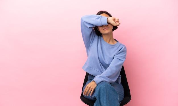 Giovane donna di razza mista seduta su una sedia isolata su sfondo rosa che copre gli occhi con le mani