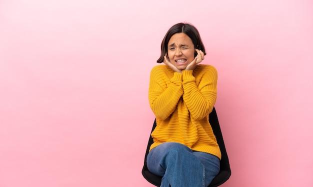 Giovane donna di razza mista seduta su una sedia isolata su sfondo rosa frustrata e che copre le orecchie