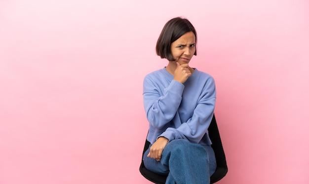Giovane donna di razza mista seduta su una sedia isolata su sfondo rosa che ha dubbi