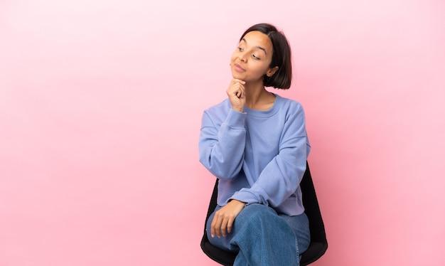 Giovane donna di razza mista seduta su una sedia isolata su sfondo rosa avendo dubbi