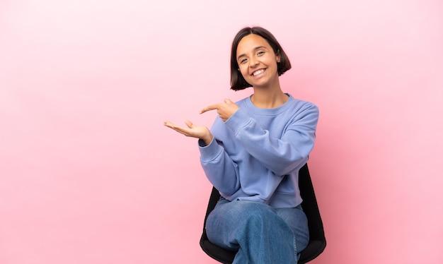 Giovane donna di razza mista seduta su una sedia isolata su sfondo rosa che tiene copyspace immaginario sul palmo per inserire un annuncio