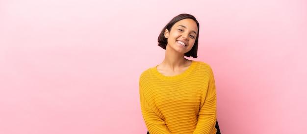 Giovane donna di razza mista seduta su una sedia isolata su sfondo rosa ridendo