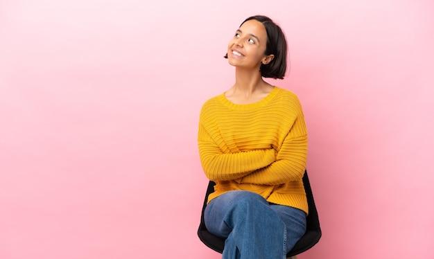Giovane donna di razza mista seduta su una sedia isolata su sfondo rosa, alzando lo sguardo mentre sorride
