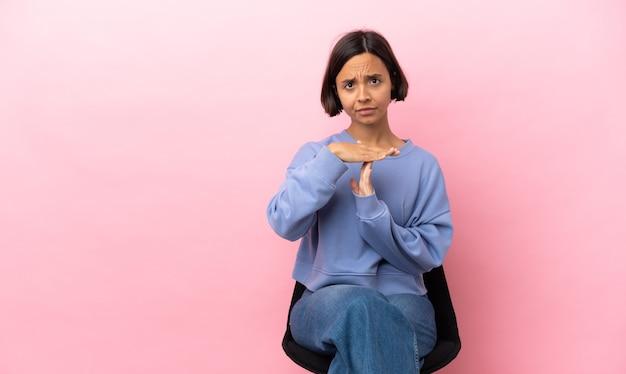 Giovane donna di razza mista seduta su una sedia isolata su sfondo rosa facendo un gesto di time out