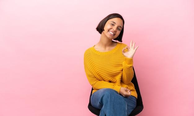 Giovane donna di razza mista seduta su una sedia isolata su sfondo rosa che mostra segno ok con le dita