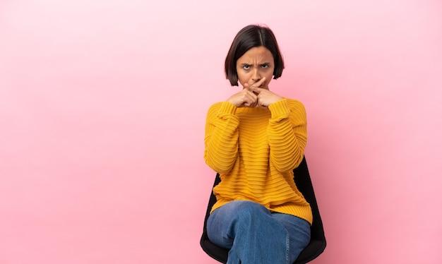 Giovane donna di razza mista seduta su una sedia isolata su sfondo rosa che mostra un segno di silenzio gesto