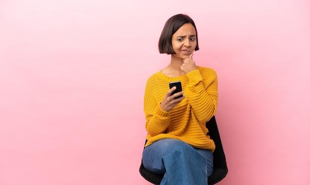 Giovane donna di razza mista seduta su una sedia isolata su sfondo rosa pensando e inviando un messaggio