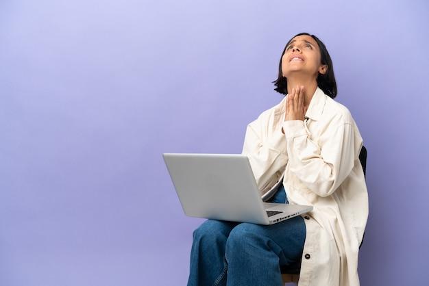 La giovane donna della corsa mista che si siede su una sedia con il computer portatile isolato su fondo porpora tiene insieme il palmo. la persona chiede qualcosa
