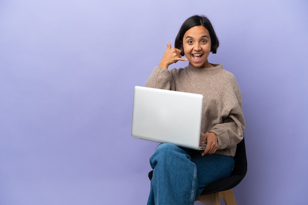 Giovane donna della corsa mista che si siede su una sedia con il computer portatile isolato su fondo porpora che fa il gesto del telefono. richiamami segno