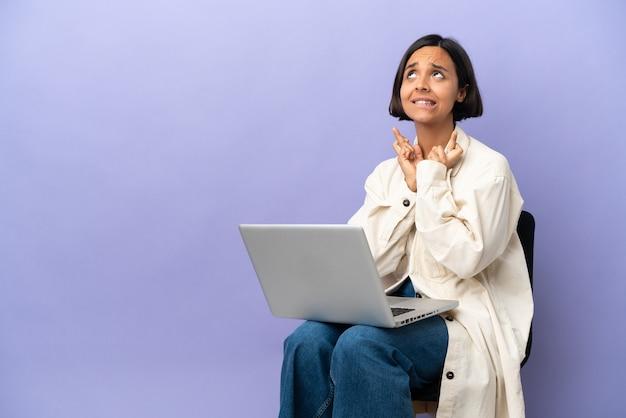 Giovane donna di razza mista seduta su una sedia con laptop isolato su sfondo viola con le dita incrociate e augurando il meglio