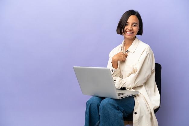 Giovane donna di razza mista seduta su una sedia con laptop isolato su sfondo viola con espressione facciale a sorpresa
