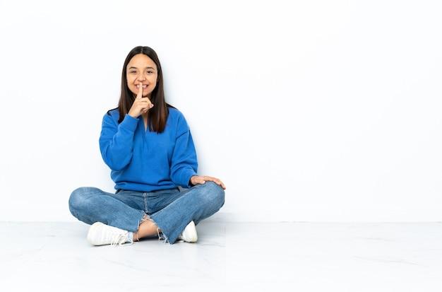 Giovane donna di razza mista seduta sul pavimento isolato su sfondo bianco che mostra un segno di silenzio gesto mettendo il dito in bocca