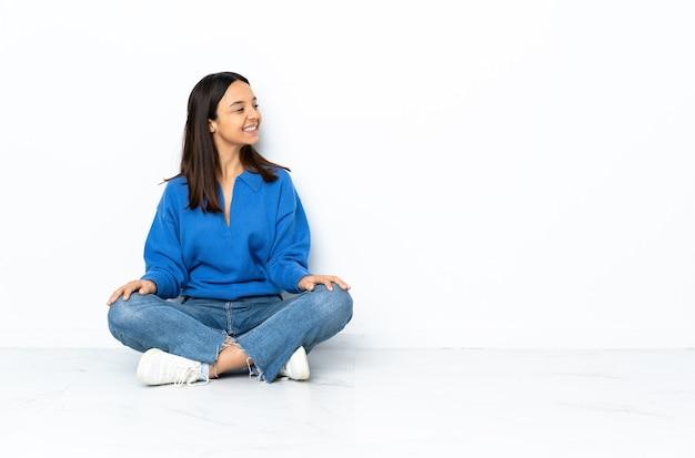 Giovane donna di razza mista seduta sul pavimento isolato sul muro bianco guardando al lato e sorridente