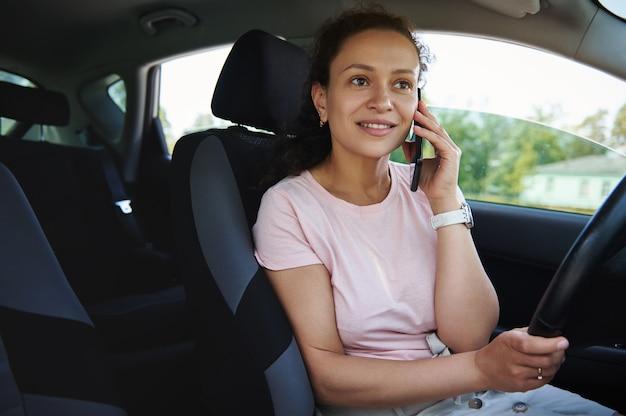 Giovane donna di razza mista che parla al telefono in macchina durante una sosta