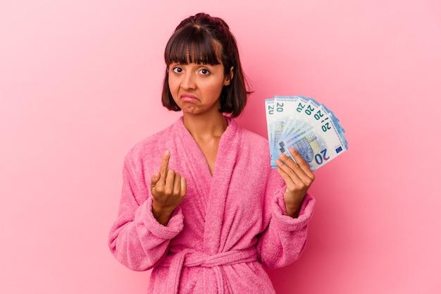 Giovane donna di razza mista che indossa un accappatoio con banconote isolate su sfondo rosa che punta con il dito verso di te come se invitasse ad avvicinarsi.