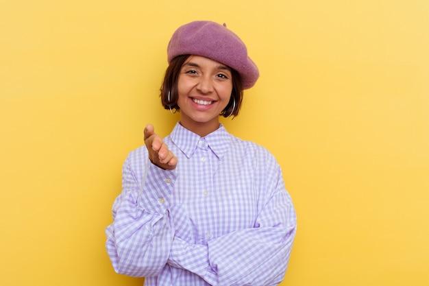 Giovane donna di razza mista che indossa un berretto isolato su sfondo giallo che allunga la mano alla telecamera in gesto di saluto.