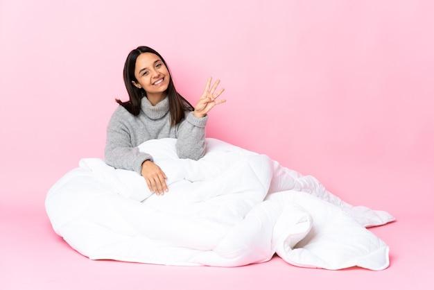 Giovane donna di razza mista che indossa pijama seduto sul pavimento felice e contando quattro con le dita