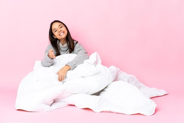 Giovane donna di razza mista che indossa pijama seduto sul pavimento si stringono la mano per chiudere un buon affare