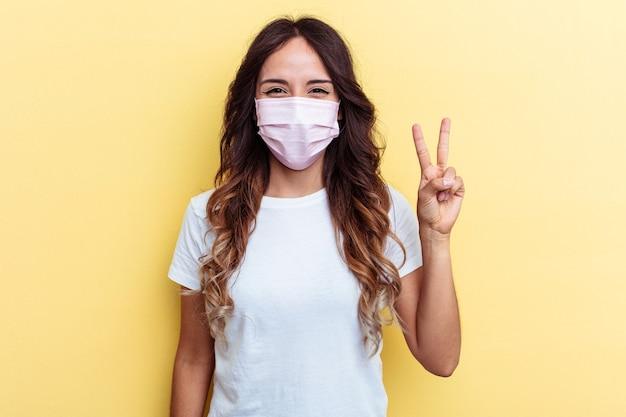 Giovane donna di razza mista che indossa una protezione per virus isolato su sfondo giallo giovane donna di razza mista che indossa una protezione per virus isolato su sfondo giallo, mostrando il numero due con le dita.