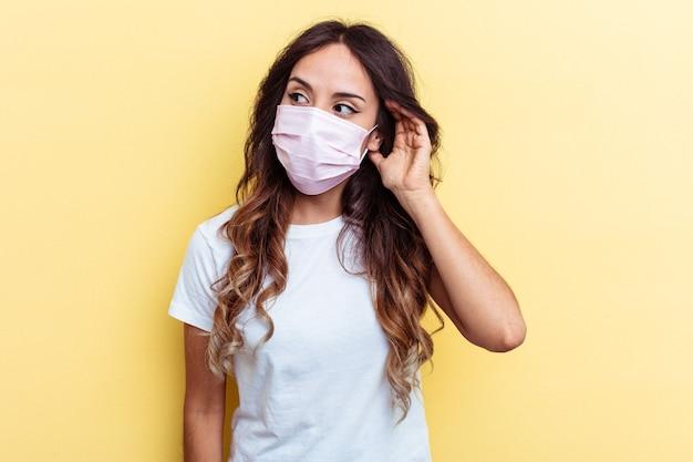 Giovane donna di razza mista che indossa una protezione per virus isolato su sfondo giallo giovane donna di razza mista che indossa una protezione per virus isolato su sfondo giallo cercando di ascoltare un pettegolezzo.