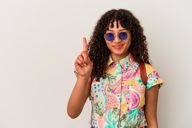 Giovane donna di razza mista che indossa occhiali da sole prendendo una vacanza isolata che mostra il numero uno con il dito.