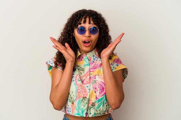 Giovane donna di razza mista che indossa occhiali da sole prendendo una vacanza isolata sorpresa e scioccata.