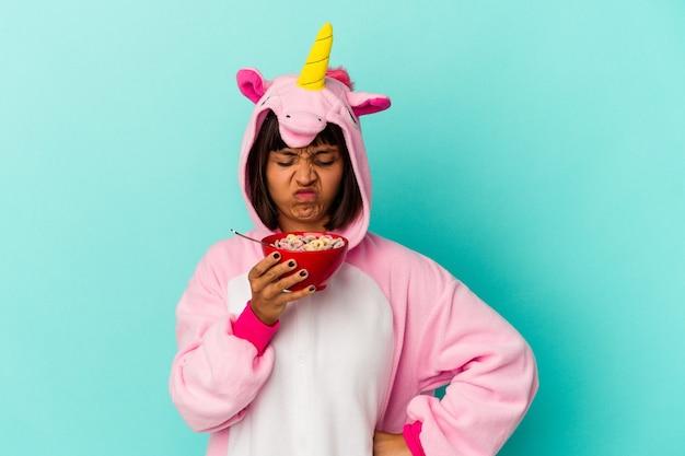 Giovane donna di razza mista che indossa un pigiama unicorno che tiene in mano un cereale isolato su sfondo blu
