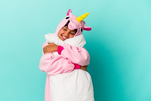 Giovane donna di razza mista che indossa un pigiama di unicorno che tiene un cuscino isolato su sfondo blu